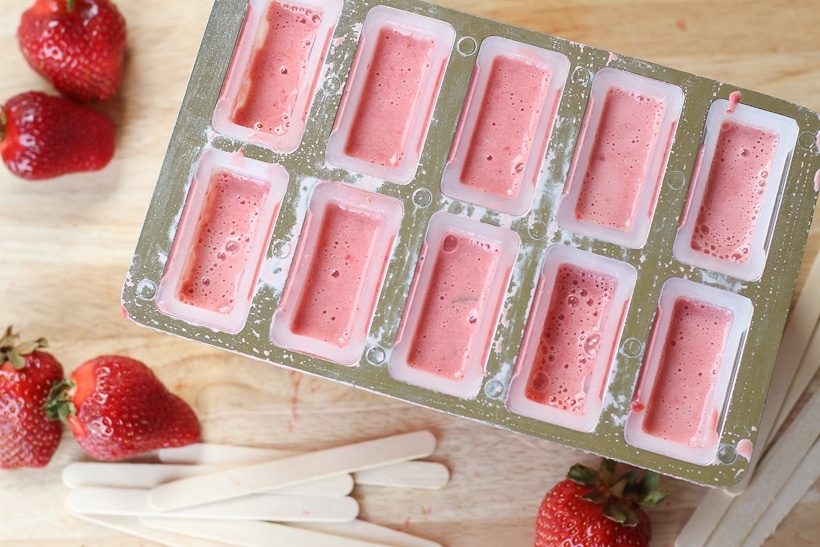 Keep cool this summer with these healthy Strawberries and Cream Popsicles.  Kids young and old will love this healthy summer snack recipe. These strawberry frozen treats won't last long. #popsicles #healthypopsicles #strawberrypopsicles #popsiclerecipe