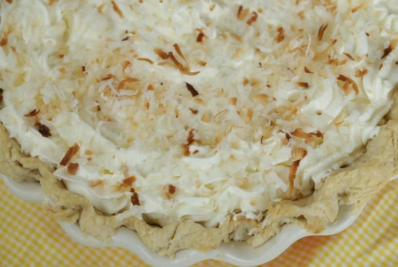 You can't go wrong with a slice of this luscious Coconut Cream Pie. This Best Coconut Custard pie recipe has a creamy coconut custard filling and topped with sweet whipped cream. All of this is nestled into a buttery, flaky pie crust. This easy pie recipe is perfect to serve all year long. #coconutcustardpie #pierecipe #easypierecipe #nobakedessert