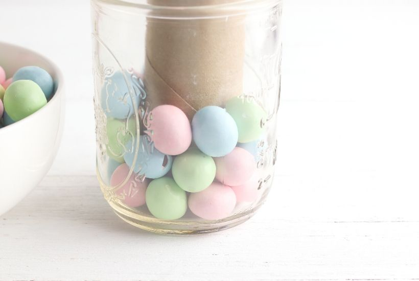 Add a touch of spring to your dining table. This easy Easter Candy Mason Jar Flower Vase is so easy to create. Grab so Easter candy and a mason jar and start crafting. You can make this easy holiday craft in just minutes. #eastercraft #holidaycraft