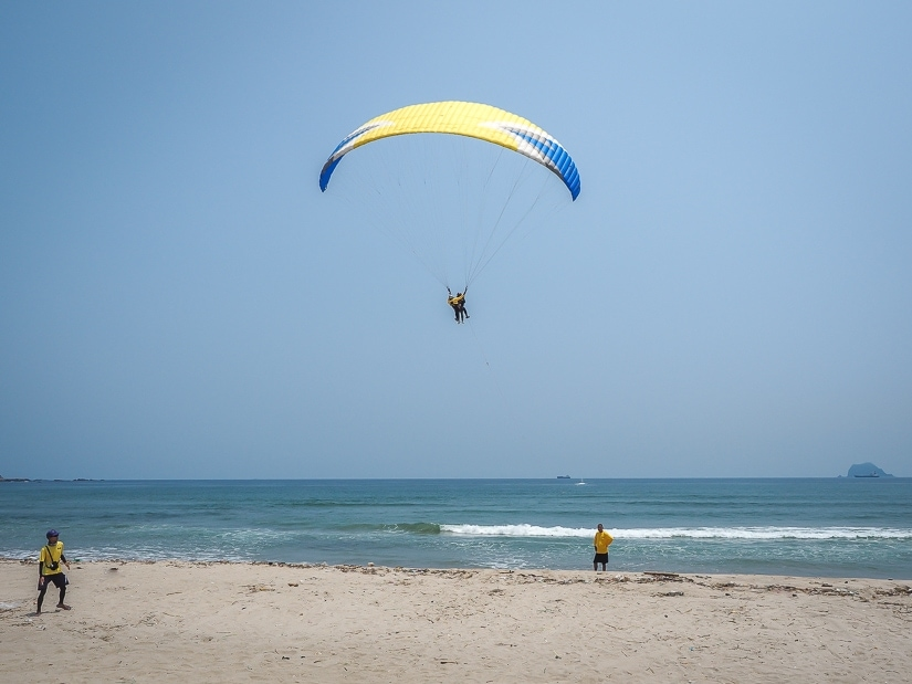 A person paragliding over Wanli beach in Taiwan in summer