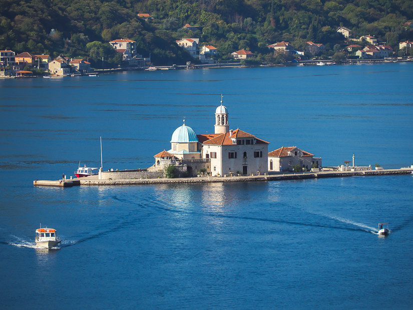 Two boats sailing away from Out Lady of the Rocks, the most famous of the places to visit in Perast