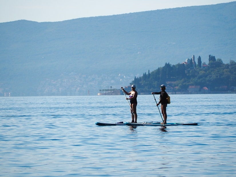 Two people stand-up paddle boarding on the Bay of Kotor
