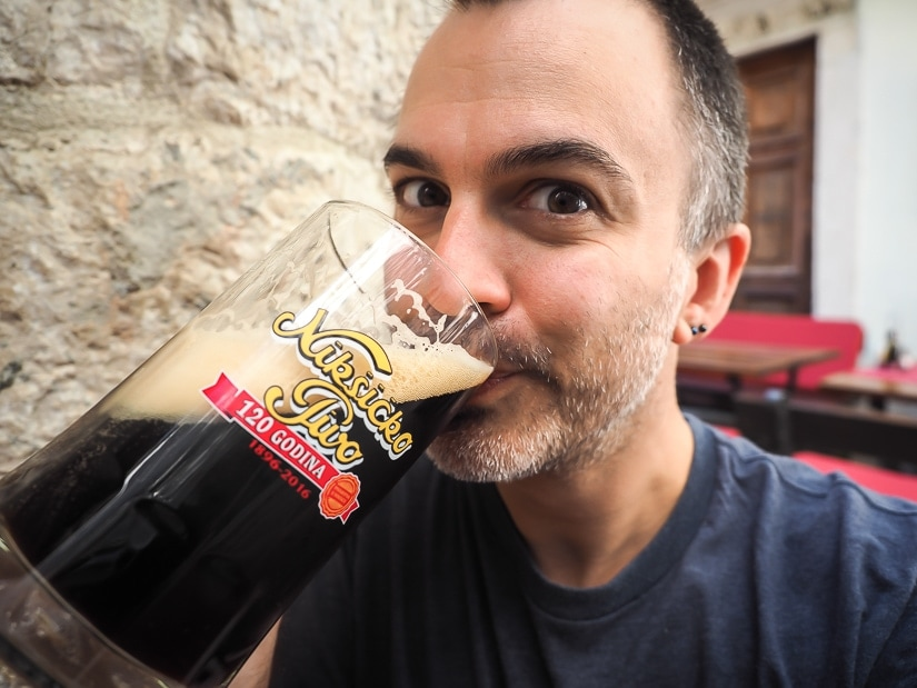 Me drinking a large glass of local Montenegro Niksicko beer at a restaurant in Kotor