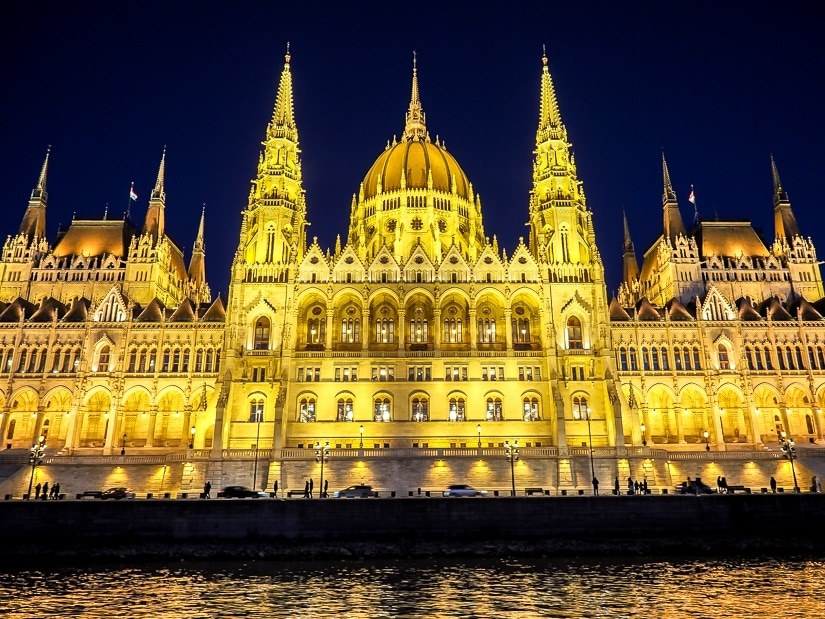 Budapest Parliament Building lit up at night, viewed from a sunset river cruise