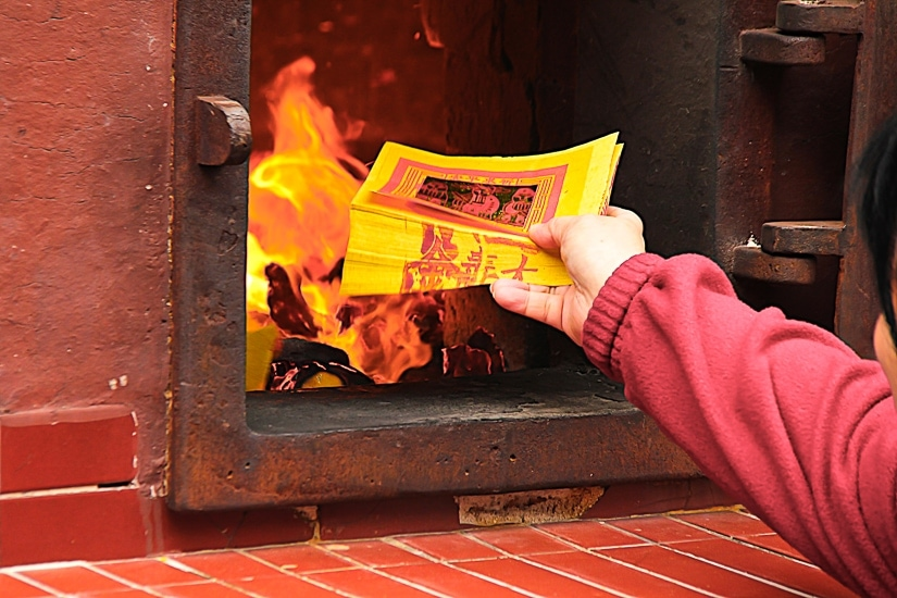 A hand putting some ghost money into a fire, part of the rituals that take place during Ghost Month in August in Taipei