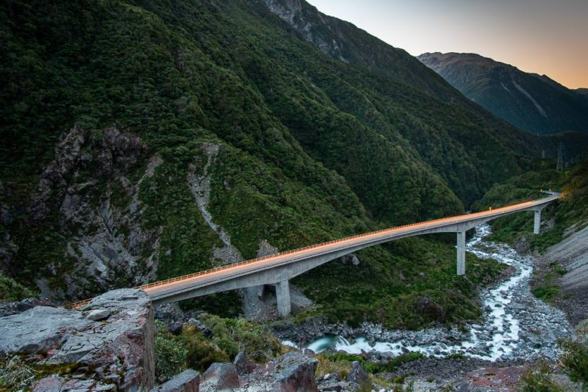 View of Otira Viaduct from the Otira Viaduct Lookout at sunset as a car drives over