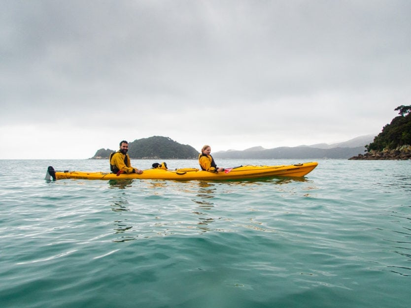 couple kayaking in abel tasman national park with tonga island in the background