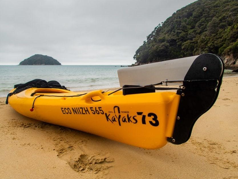 Abel Tasman Kayaks sea kayak on part of the Abel Tasman Coast Track near Onetahuti Bay with Tonga Island in the background