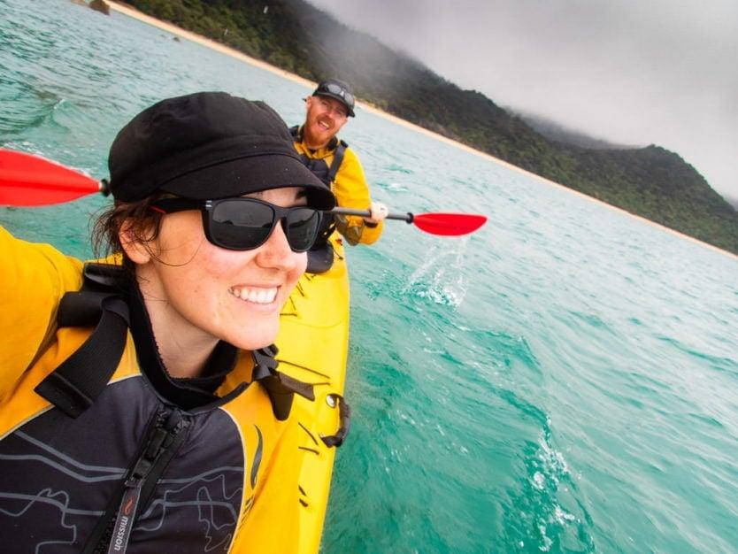 couple taking a selfie while kayaking in Mosquito Bay in Abel Tasman National Park