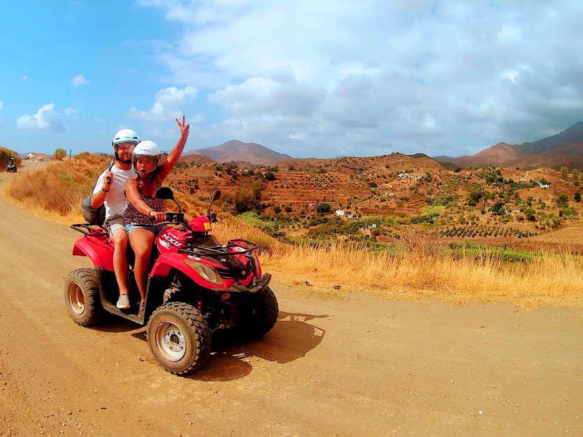 a woman is excited to be riding a quad with a hand up