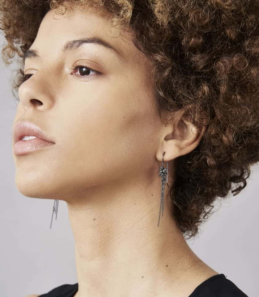 Photo of model wearing diamond and oxidised silver chain earrings.