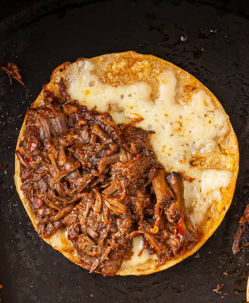 quesabirria taco cooking in a skillet