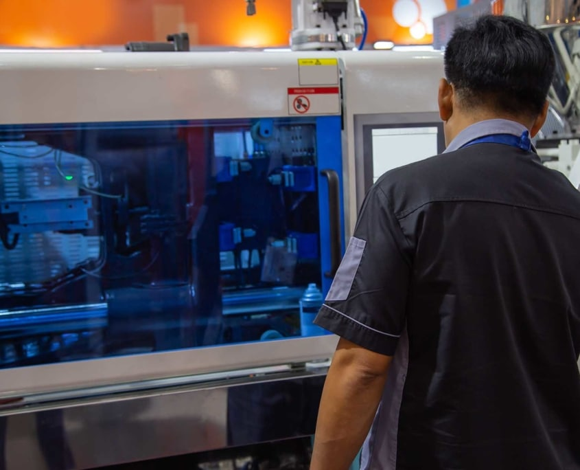 Plastic Injection Molding Worker using large machine