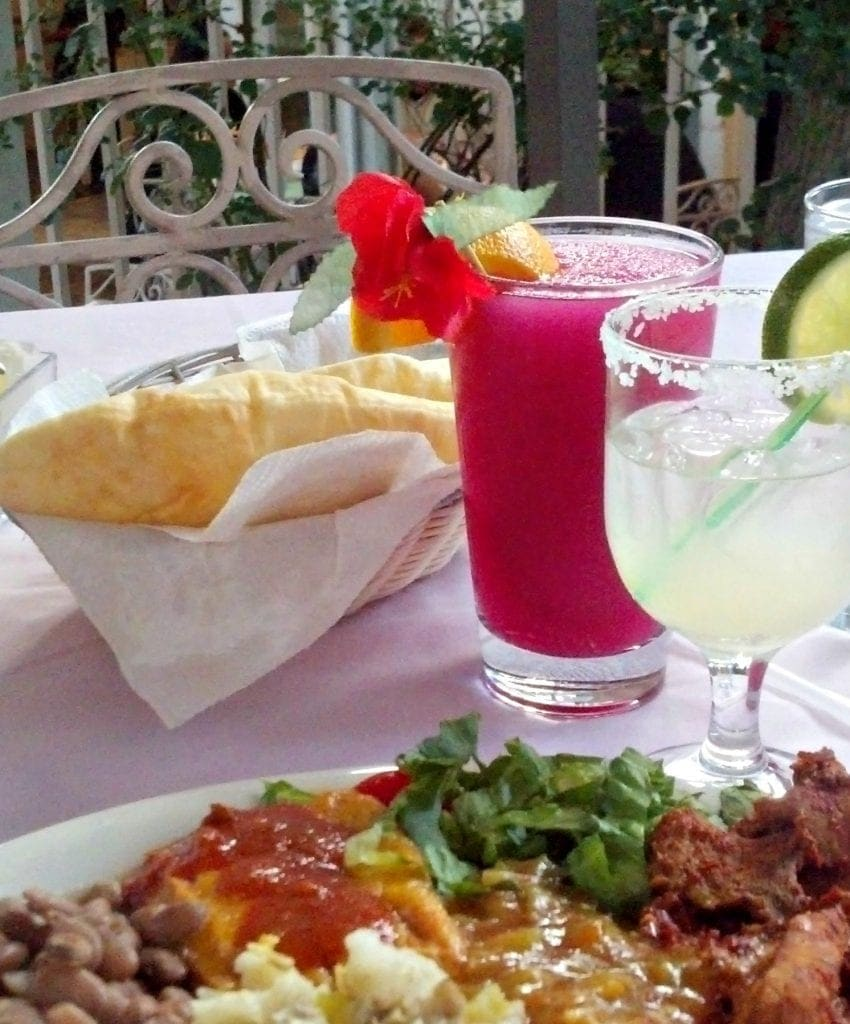 table with light pink table linens has plate of of food in foreground, margaritas and sopapilla in background - outdoors with elegant metal chair