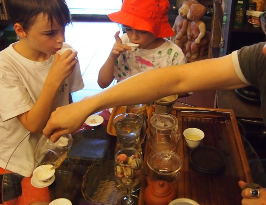 "Things to do in KL with Kids Tasting Tea in Kual Lumpur with kids"" class=""wp-image-43525"" srcset=""https://cdn.shortpixel.ai/client/q_glossy,ret_img,w_850/https://worldtravelfamily.com/wp-content/uploads/2020/01/Tasting-Tea-in-Kual-Lumpur-with-kids.jpg 850w, https://cdn.shortpixel.ai/client/q_glossy,ret_img,w_300/https://worldtravelfamily.com/wp-content/uploads/2020/01/Tasting-Tea-in-Kual-Lumpur-with-kids-300x232.jpg 300w, https://cdn.shortpixel.ai/client/q_glossy,ret_img,w_768/https://worldtravelfamily.com/wp-content/uploads/2020/01/Tasting-Tea-in-Kual-Lumpur-with-kids-768x594.jpg 768w, https://cdn.shortpixel.ai/client/q_glossy,ret_img,w_735/https://worldtravelfamily.com/wp-content/uploads/2020/01/Tasting-Tea-in-Kual-Lumpur-with-kids-735x568.jpg 735w"" sizes=""(max-width: 850px) 100vw, 850px"
