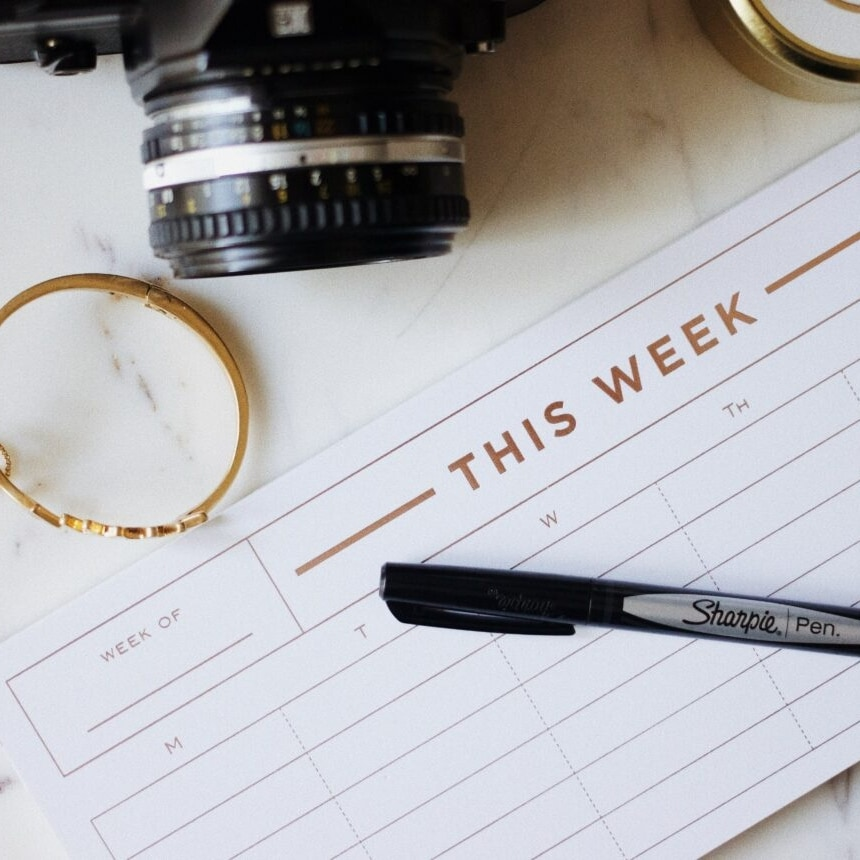 Picture of a calendar with the words this week with a sharpie pen on top next to some jewelry and a camera used for the blog post when and where to post