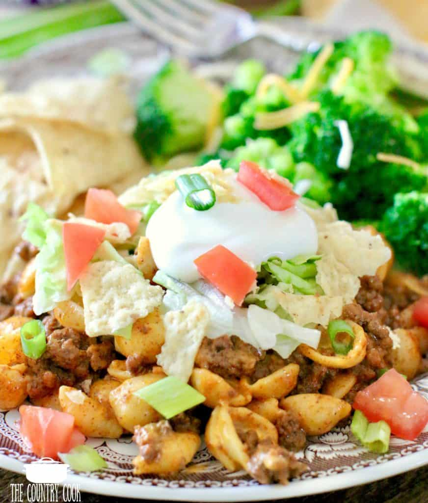 Taco Mac and Cheese with lettuce, tomato, tortilla chips and sour cream