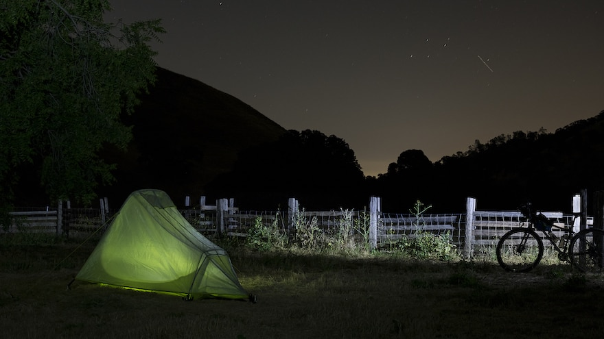 A bike next to a tent in a dark field on a starry night
