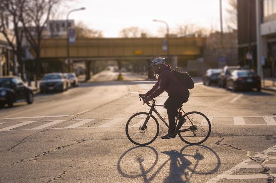 A bike commuter rides across a street in winter