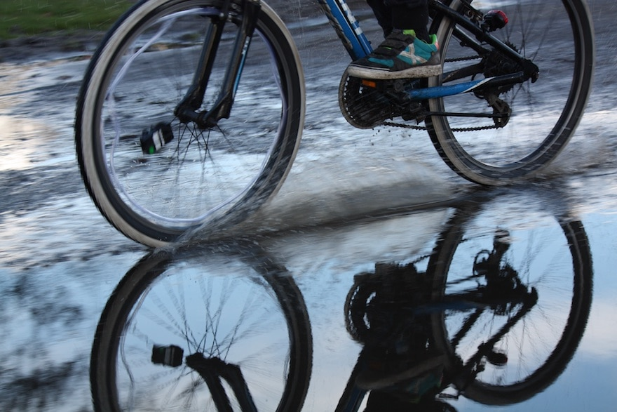 A pair of bicycle wheels slicing through a deep puddle