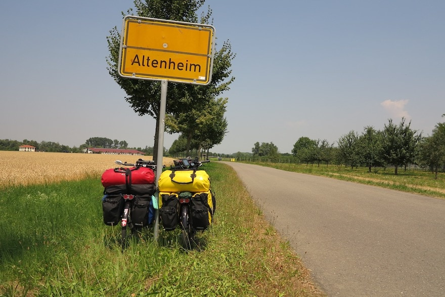 Two touring bikes parked at the side of a long straight road headed toward Allenheim