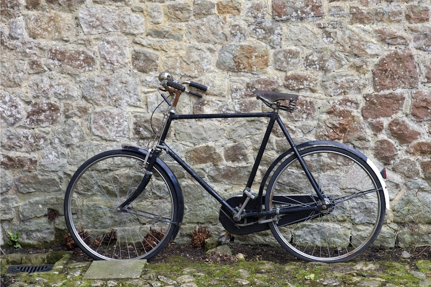 Side view of a bicycle with a chain guard, leaning against a stone wall