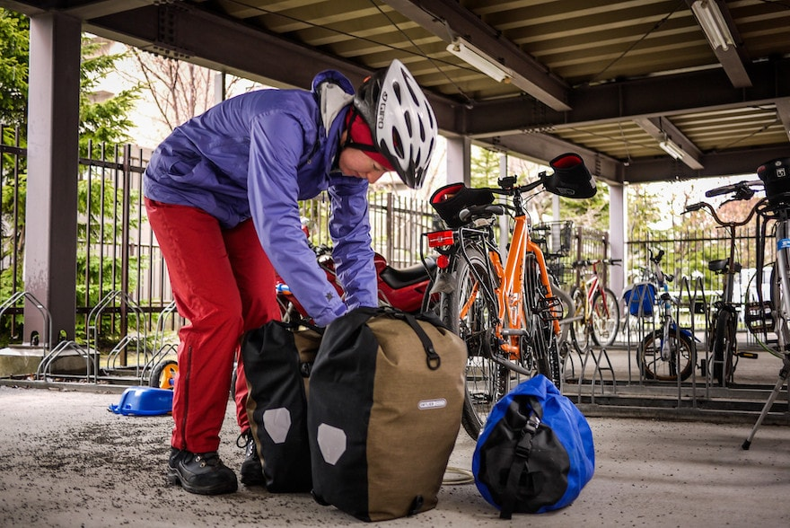 A cyclist digging into her pannier bags after parking her bike