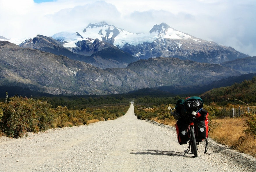 A bike packed with supplies stopped on a gravel road leading to snowy mountains