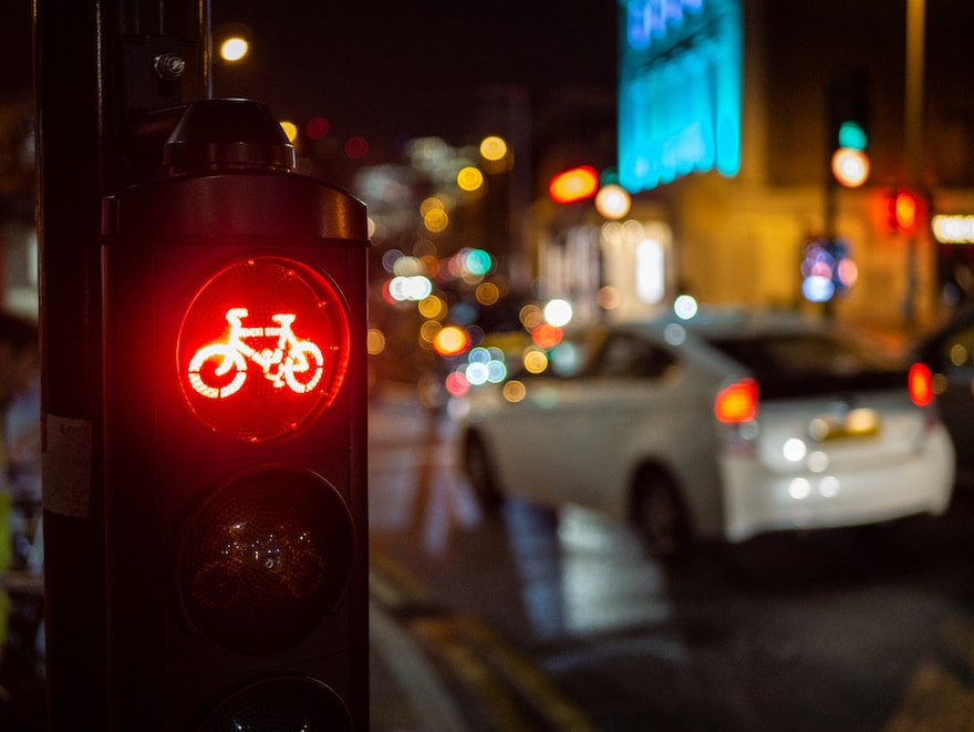 Closeup of a red stop light on a bike route with traffic in the background