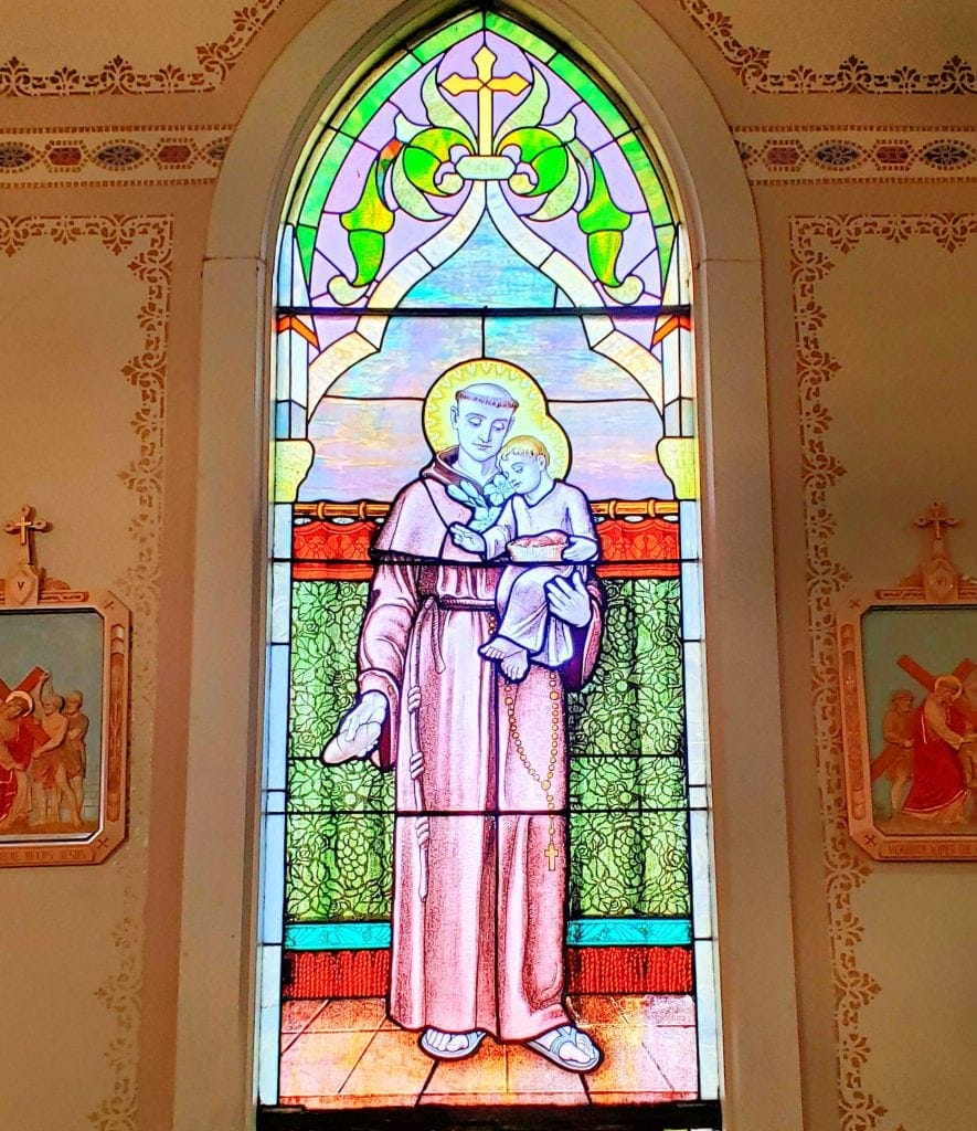 stained glass window at St Matthias Church that depicts St Anthony holding the Christ child and bread