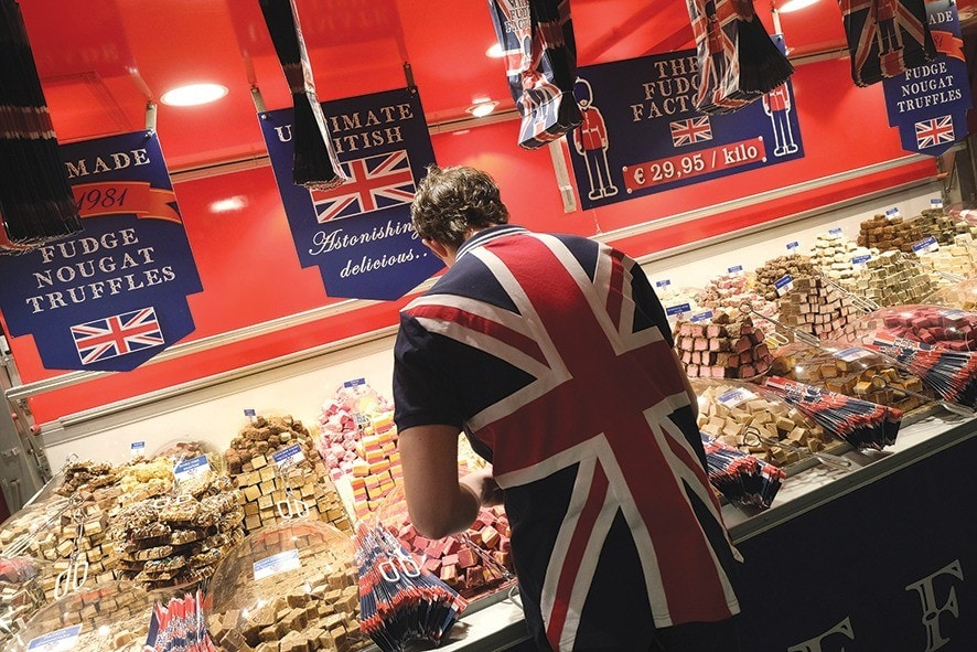 BERLIN, GERMANY - JANUARY 21: A sales assistant wearing a British flag arranges fudge at a British fudge manufacturer's stand at the International Green Week agricultural trade fair on January 21, 2019 in Berlin, Germany. The future of trade between the UK and the European Union is uncertain following the recent overwhelming rejection of British Prime Minister Theresa May's Brexit deal in the House of Commons last week. The International Green Week (Internationale Grüne Woche), among the biggest trade fairs of its kind, focuses on agriculture, horticulture and foods. (Photo by Sean Gallup/Getty Images)