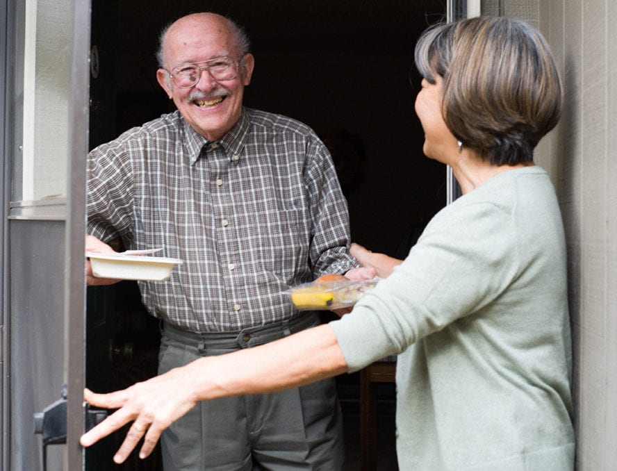 Meals on Wheels People representative delivers food to an elderly man at his front door.