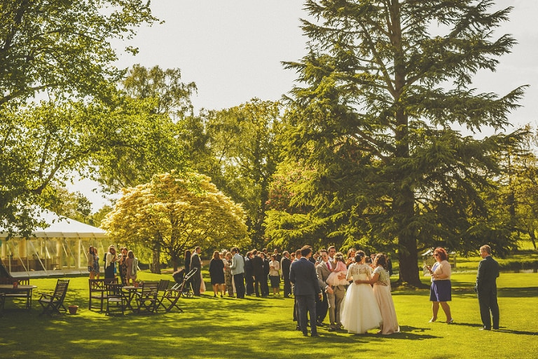 The bride and groom drinking with friends and family in the garden at Longstowe Hall