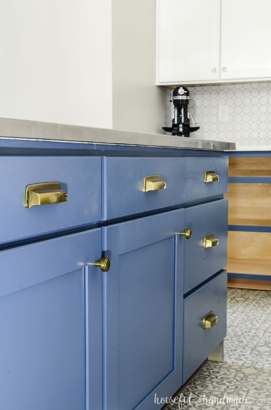Brass knobs and pulls are perfect on the navy blue base cabinets. See the complete budget farmhouse kitchen remodel at housefulofhandmade.com.