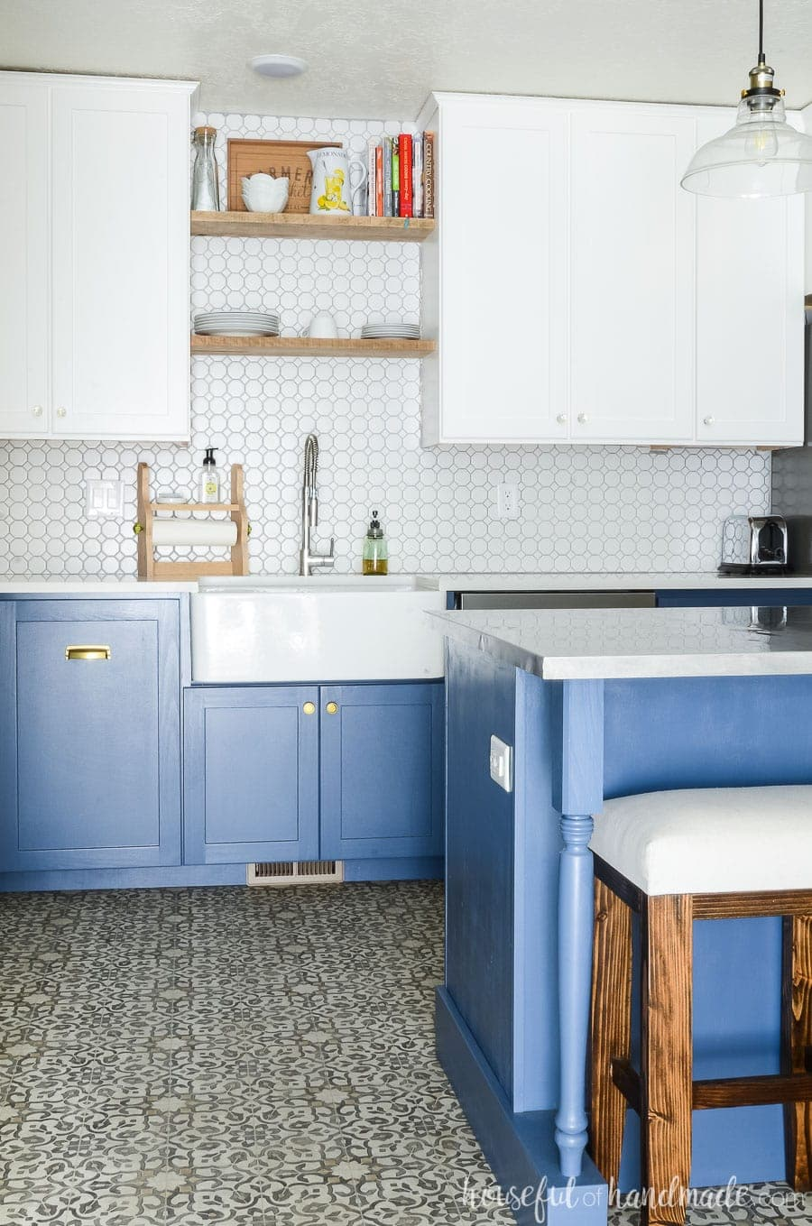 Two tone kitchen with white upper cabinets and blue base cabinets. Apron front kitchen sink with rustic open shelving. Patterned vinyl flooring.