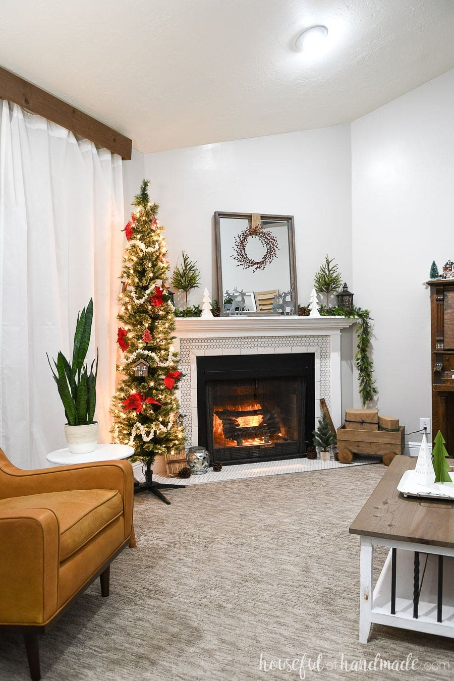 Full view of the living room decorated for the Classic Christmas home tour. Pencil tree next to the fireplace decorated with poinsettias and popcorn garland.