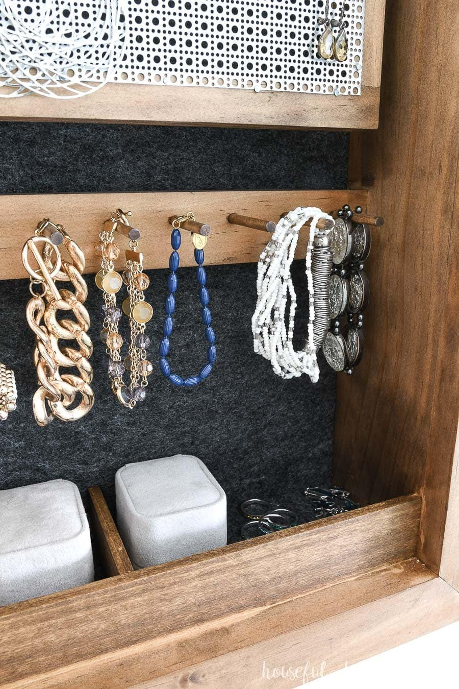 Close up view of bracelet hooks and ring compartments of the DIY wall jewelry organizer.