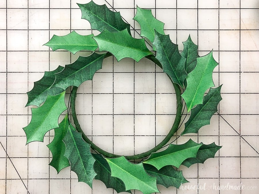 Fold the leaves of the paper holly wreath down around the embroidery hoop to create a wreath shape.