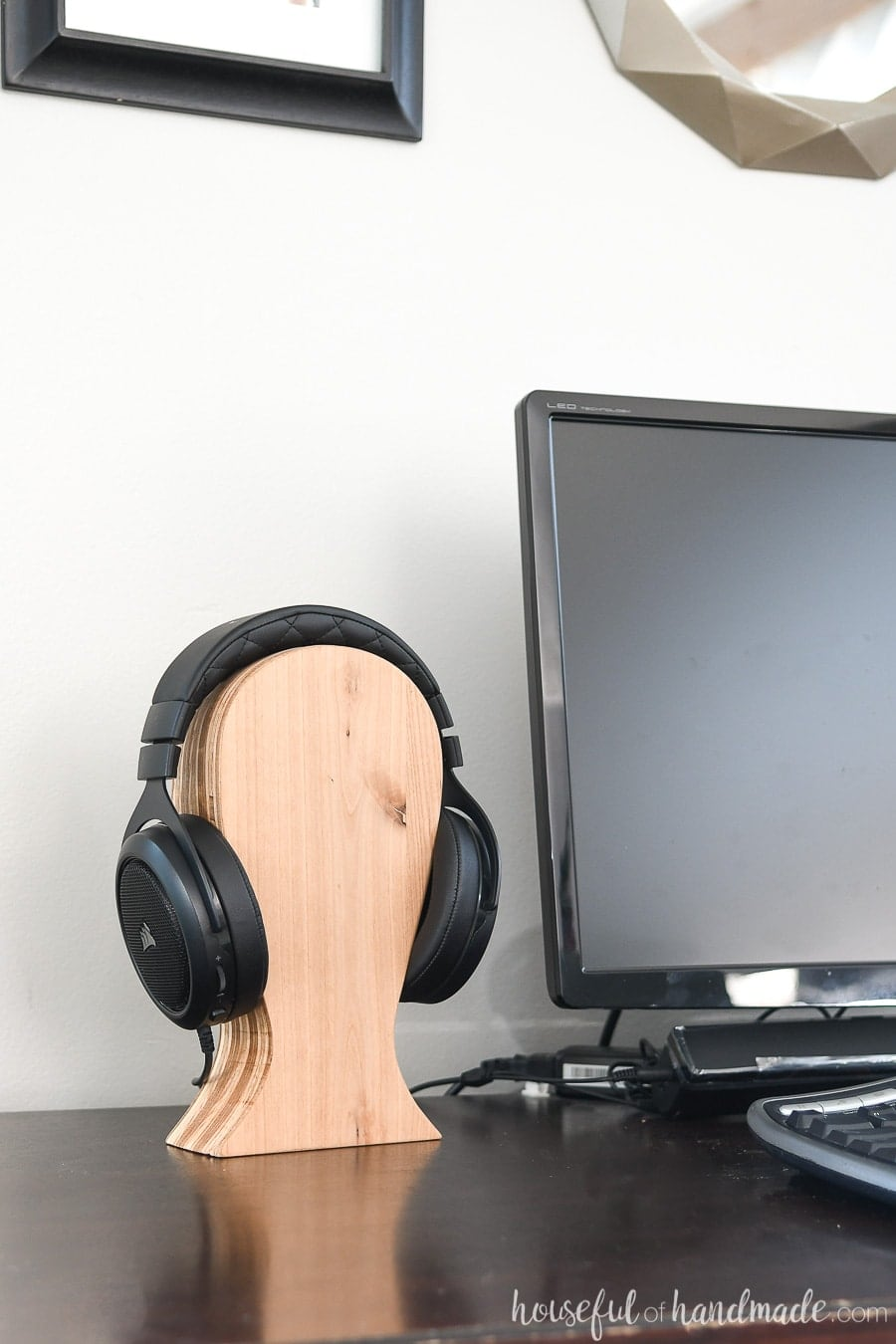 DIY headphone stand made from plywood scraps on a desk.