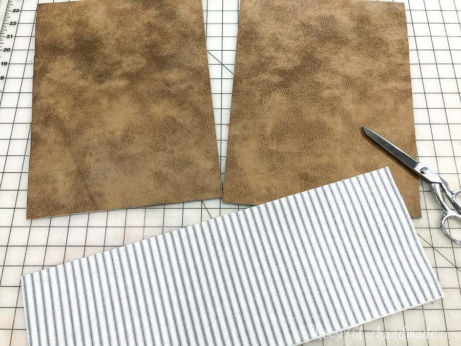 Piece of fabric and leather cut out for the DIY leather throw pillows.