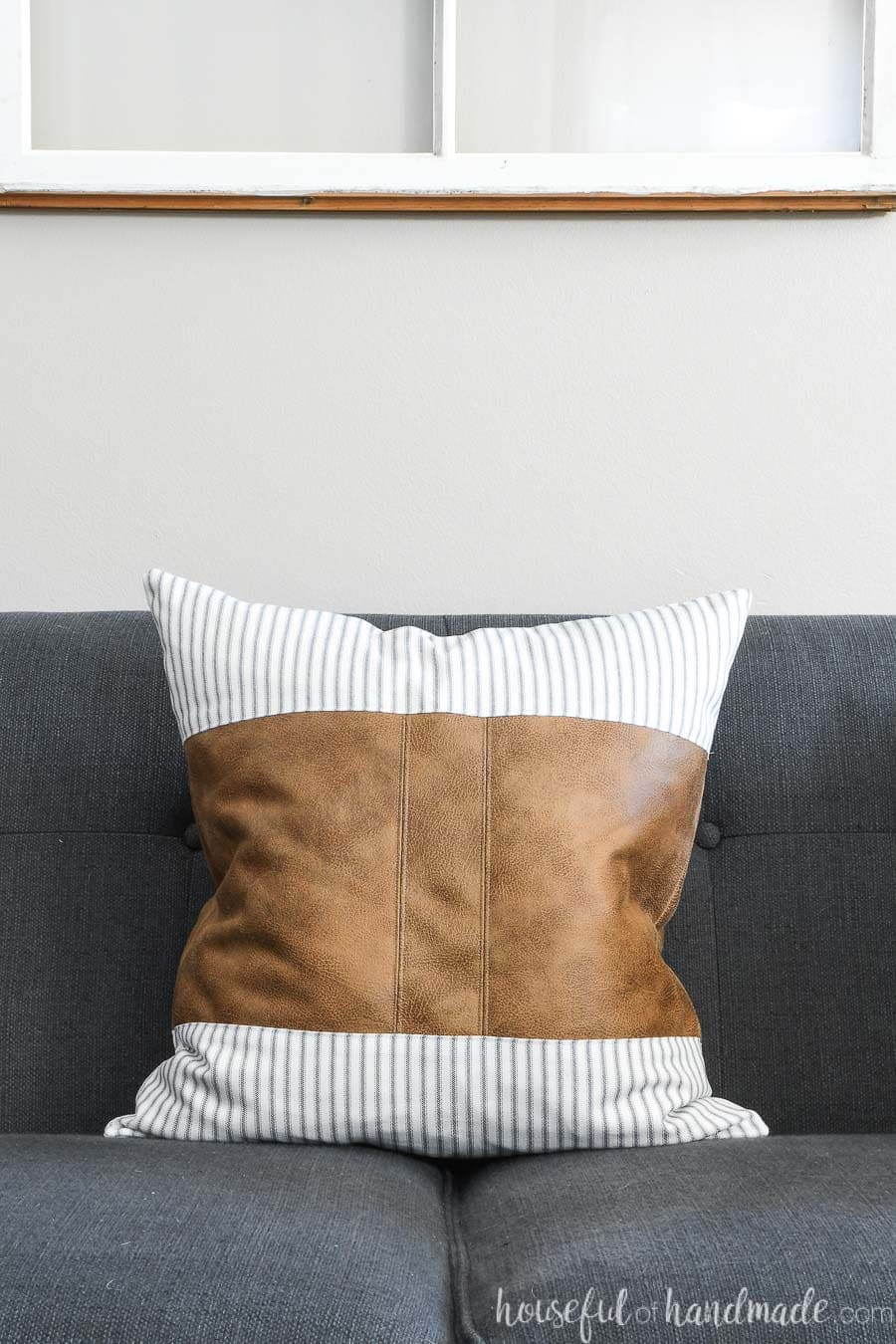 Leather pillow cover with center stripe and ticking fabric on a navy sofa.