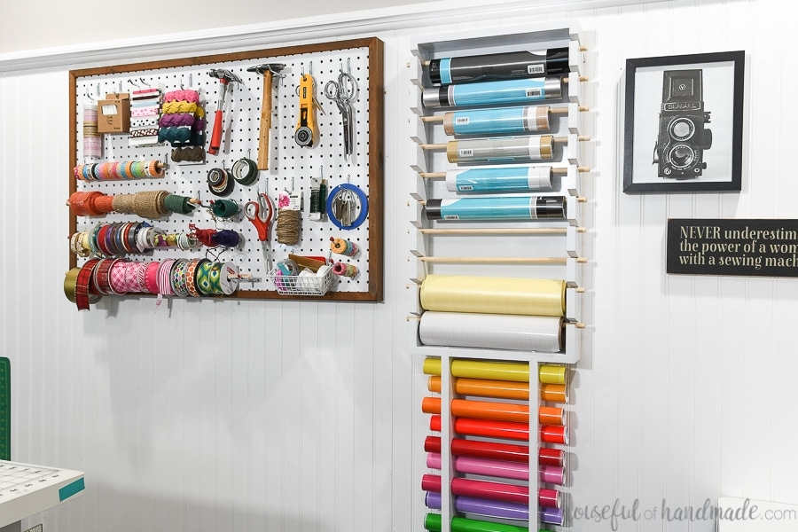 Craft room wall with pegboard storage and vinyl roll storage hanging on it.
