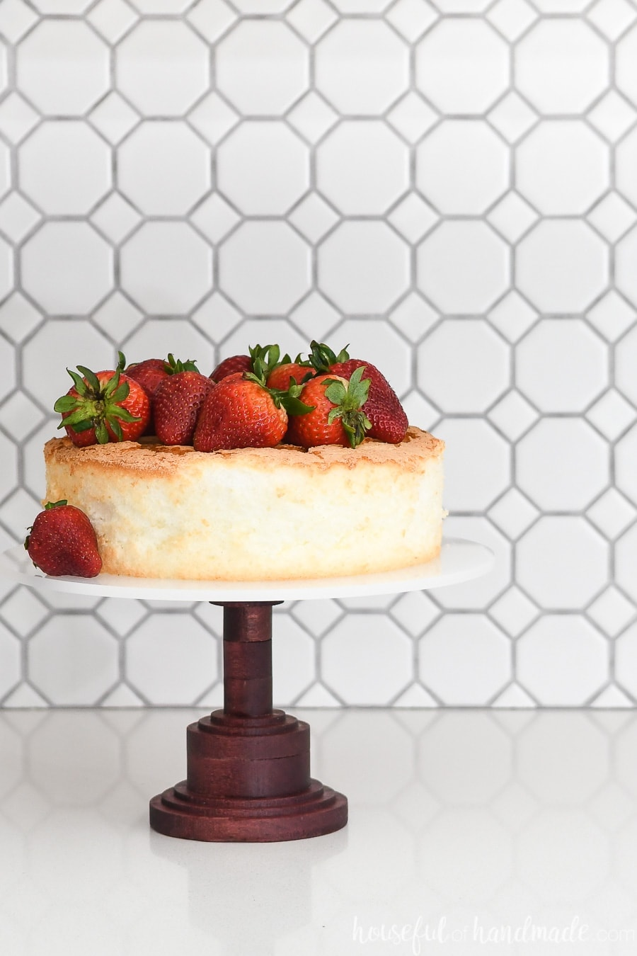 DIY cake stand made with a Purple Heart base and acrylic top with an angel food cake and strawberries on top.