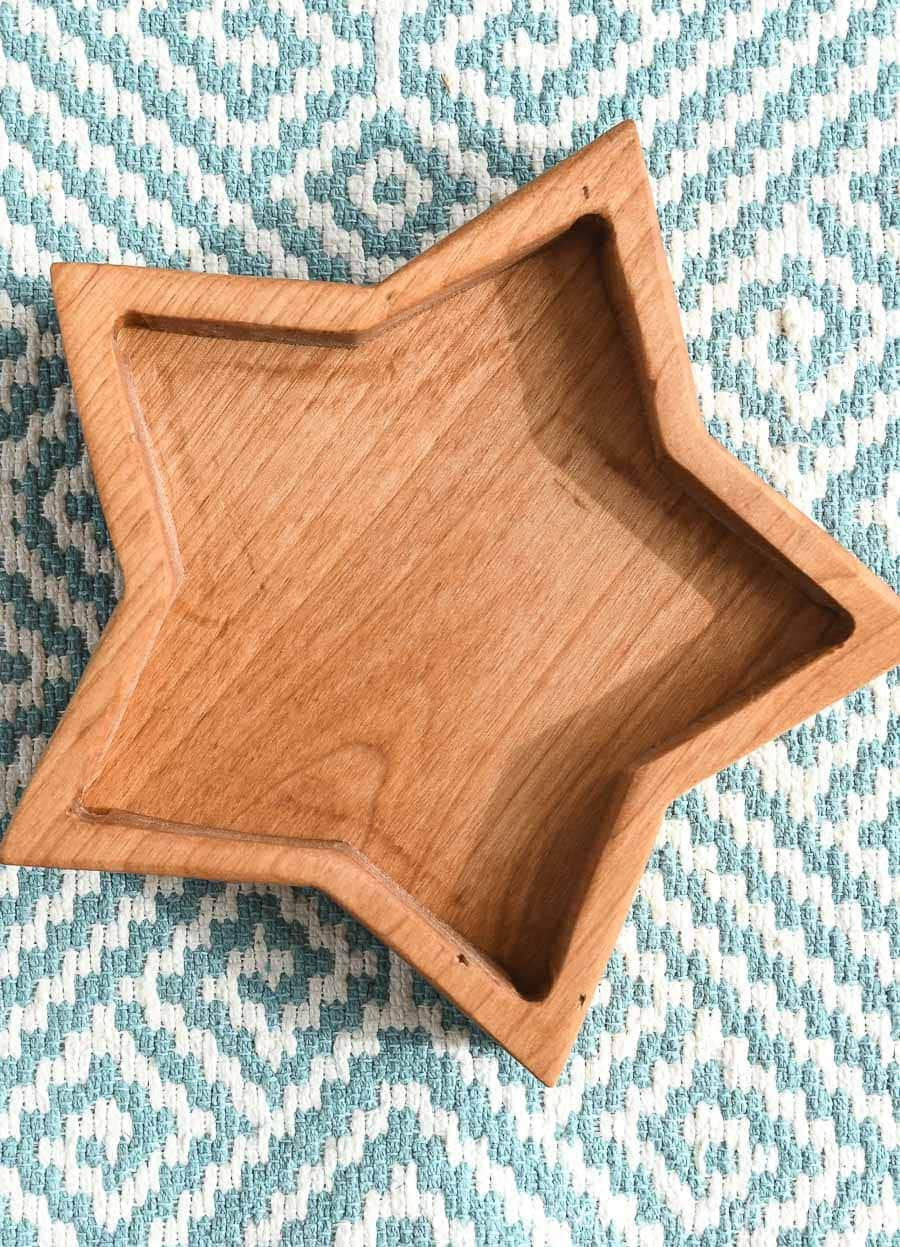 One wood star shaped box on a blue and white fabric background