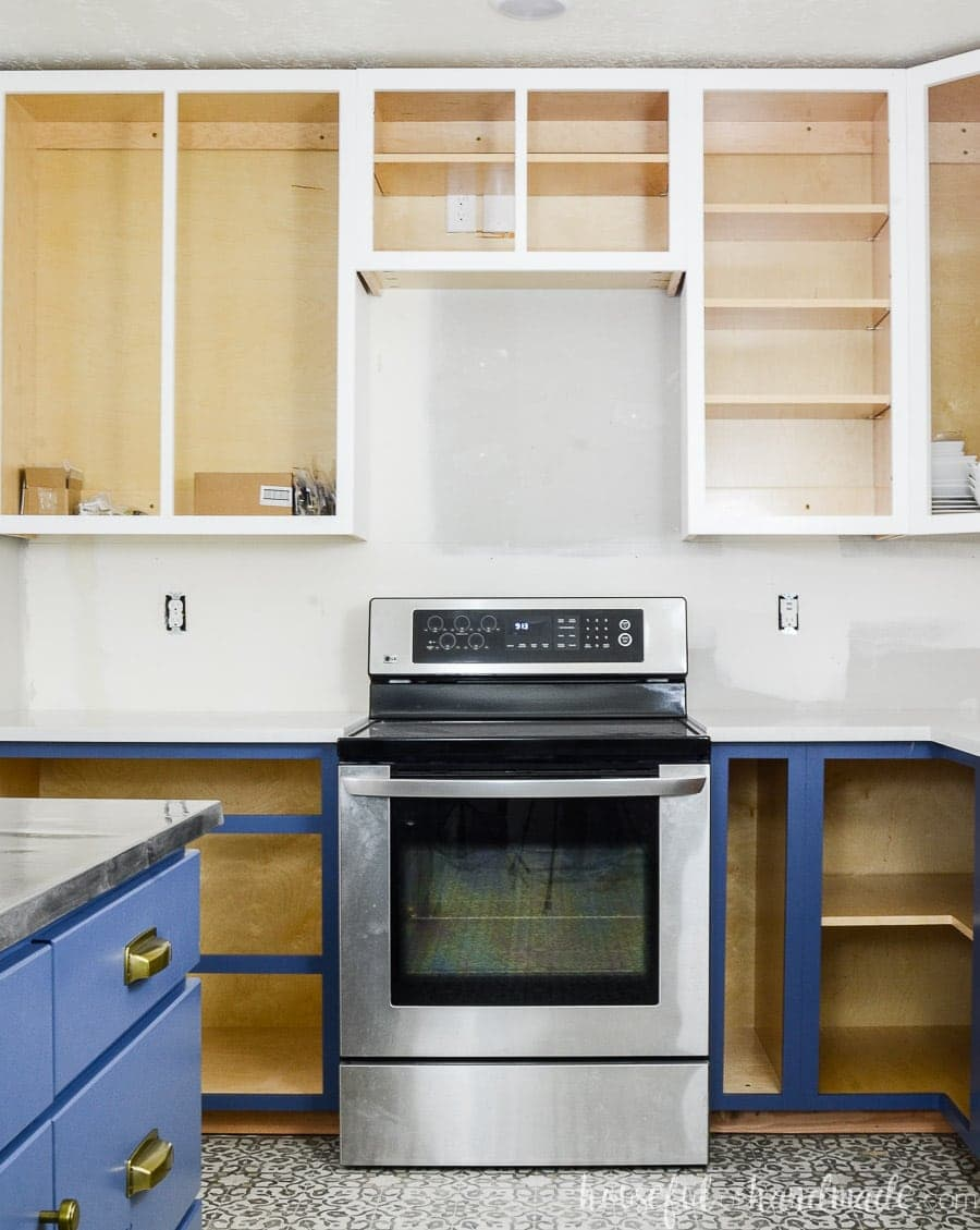 Learn how to build cabinets like these white and blue cabinets around the stove in our kitchen remodel.