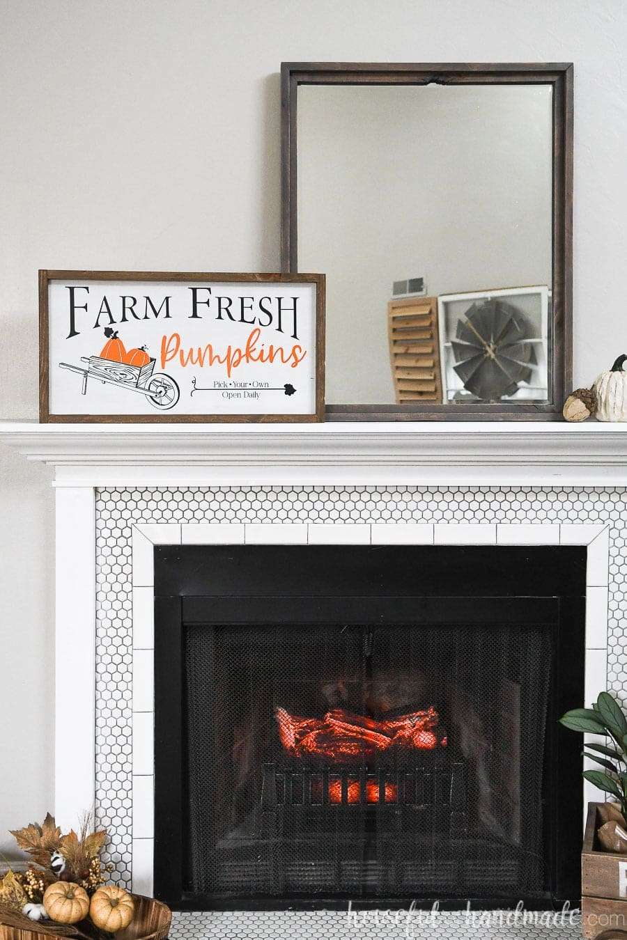 Mantel with fall decoration on it: a wood pumpkin patch sign, pumpkin, acorn, mirror, and fall leaves.