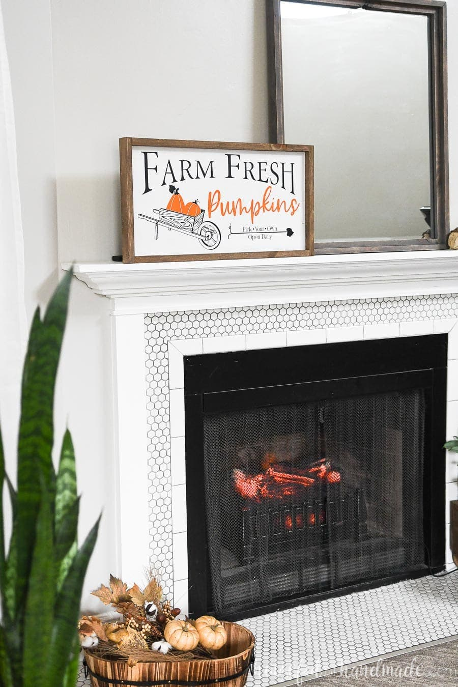 Angled view of a mantel decorated for fall with a fall wood sign and snake plant in the foreground.