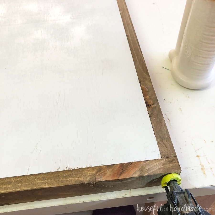 Attaching the side frame pieces of the wood sign with finishing nails.