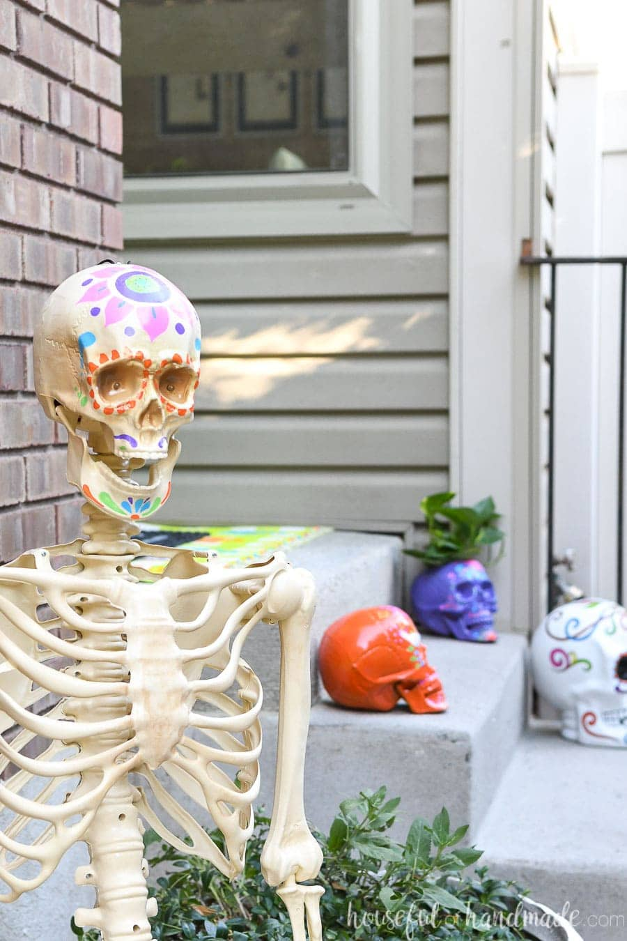 Halloween skeleton decorated to look like a sugar skull in front of porch decorated with more sugar skulls.