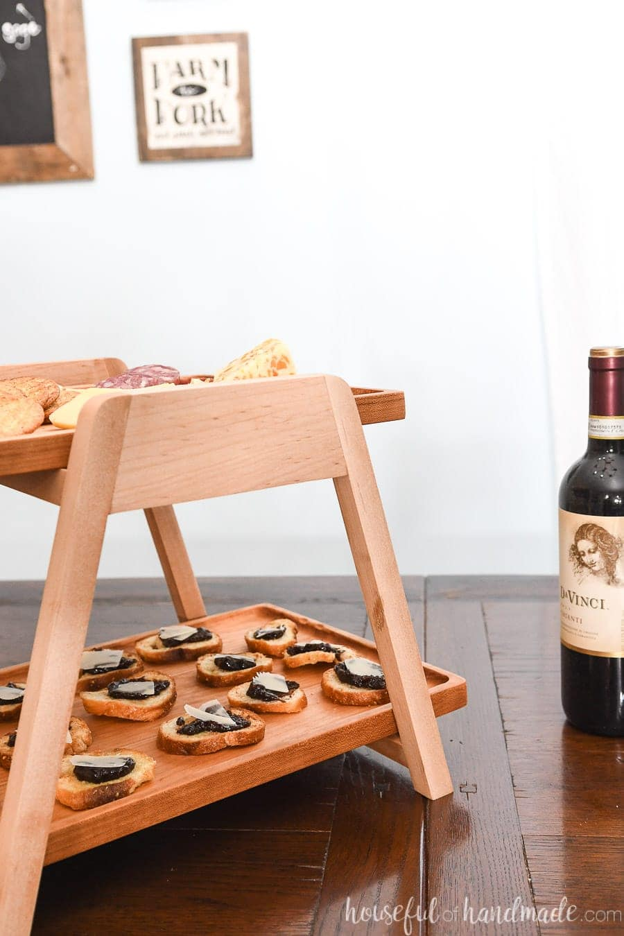 Two tier wood serving tray with appetizers on it next to a wine bottle.